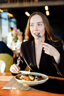 Mulher jovem bonita comendo salada em um café