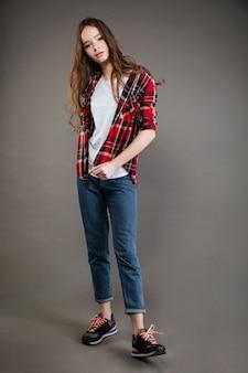 Mulher jovem bonita confiante em pé de camisa xadrez e calça jeans