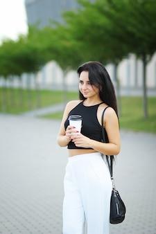 Mulher jovem bonita de negócios bebe café perto do prédio de escritórios