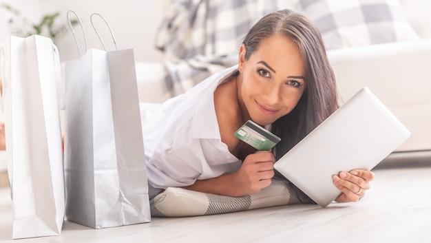 Mulher jovem bonita deitada no chão com um travesseiro debaixo dela, segurando um tablet e um cartão de crédito, olhando para a câmera, com sacolas de papel ao seu lado, sorrindo.