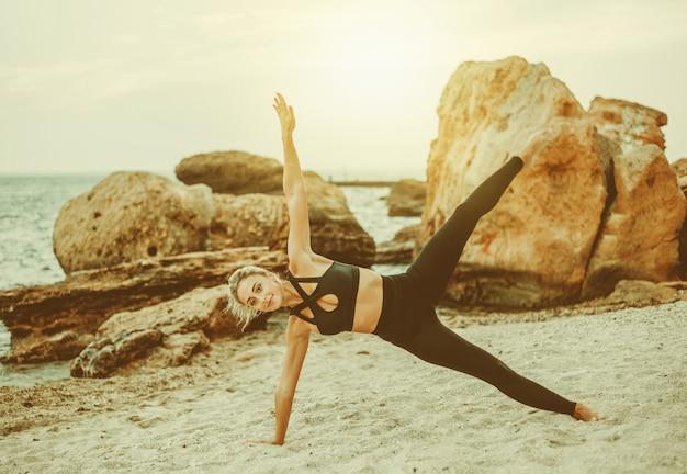Mulher jovem bonita do esporte no sportswear praticando exercícios de asana na areia na praia selvagem. treino de ioga ao ar livre