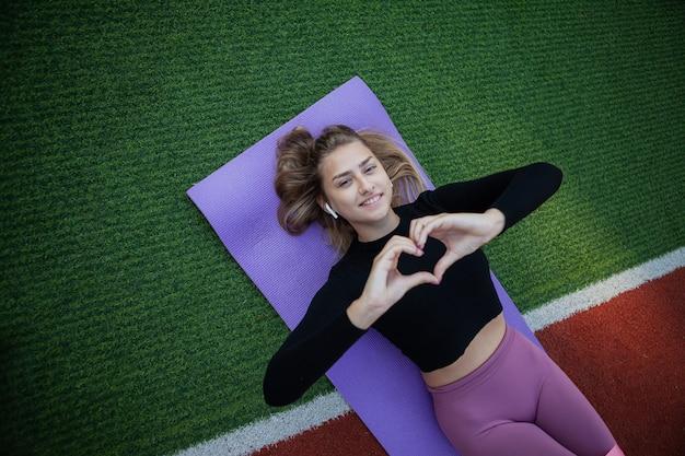 Mulher jovem bonita do esporte repousa sobre o tapete e mostra a forma do coração com os dedos. eu amo treinar