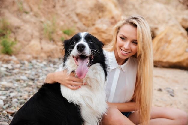 Mulher jovem bonita e alegre abraçando o cachorro na praia
