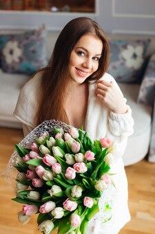Mulher jovem bonita e atraente com um lindo grande buquê de flores para tulipas. feliz dia das mães! manhã perfeita.