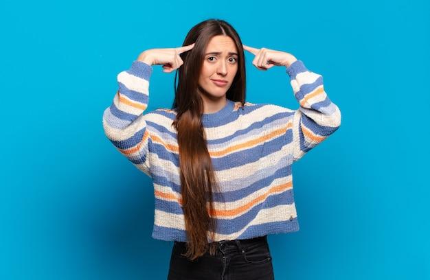Mulher jovem, bonita e casual com um olhar sério e concentrado, fazendo um brainstorming e pensando sobre um problema desafiador
