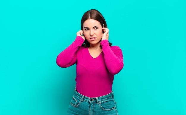 Mulher jovem, bonita e casual, parecendo zangada, estressada e irritada, cobrindo os ouvidos com um barulho, som ou música alta ensurdecedores