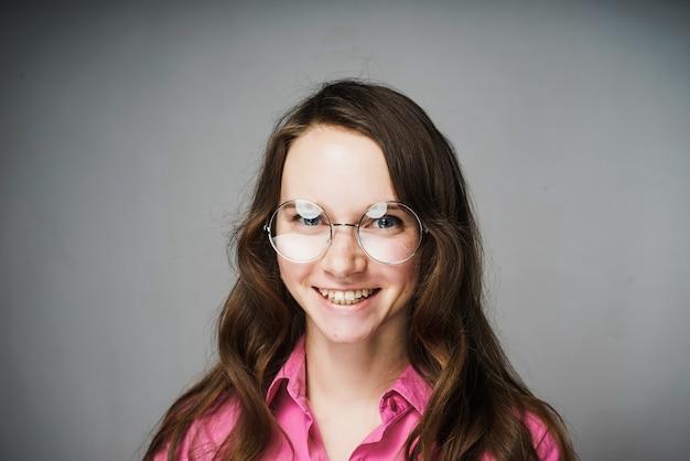 Mulher jovem bonita e feliz, trabalhadora de escritório em uma camisa rosa e óculos sorrindo