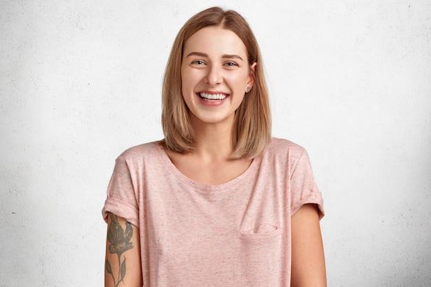 Mulher jovem bonita e sorridente feliz com poses de sorriso positivas em ambientes internos contra um espaço de cópia em branco, expressa felicidade