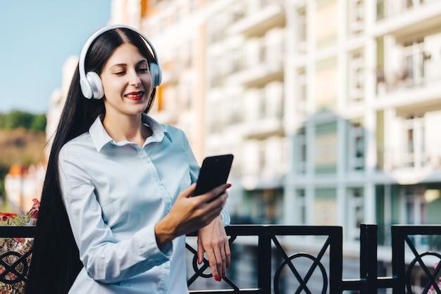 Mulher jovem, bonita e sorridente, vestida de maneira casual, em pé na varanda na rua da cidade velha, apreciando a vista e ouvindo música no celular