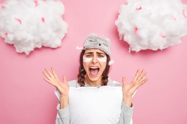 Mulher jovem bonita e zangada grita bem alto mantém a boca aberta levanta as mãos e usa pijama
