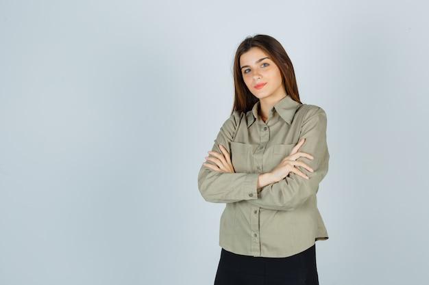 Mulher jovem bonita em pé com os braços cruzados na camisa, saia e parecendo confiante. vista frontal.