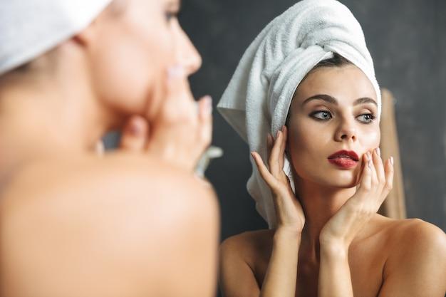 Mulher jovem bonita enrolada em uma toalha de banho em pé no banheiro
