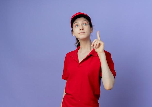 Mulher jovem, bonita, entregadora, impressionada, usando uniforme vermelho e boné levantando o dedo olhando para cima
