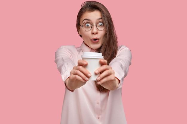 Mulher jovem bonita espantada com olhar surpreso estende as mãos com café para viagem, vestida com camisa formal, fica de queixo caído, vestida com elegância
