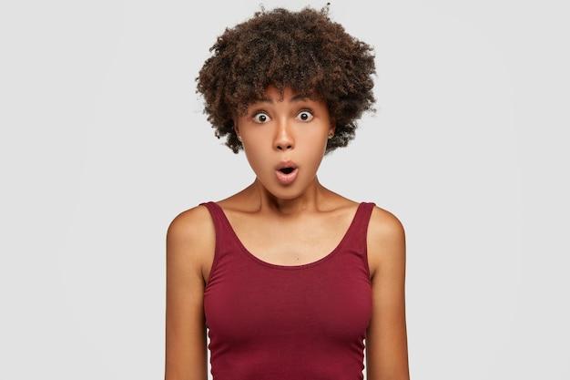 Mulher jovem bonita espantada com um corte de cabelo afro, pele morena saudável