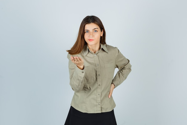 Mulher jovem bonita esticando a mão em gesto de questionamento na camisa, saia e olhando sério. vista frontal.