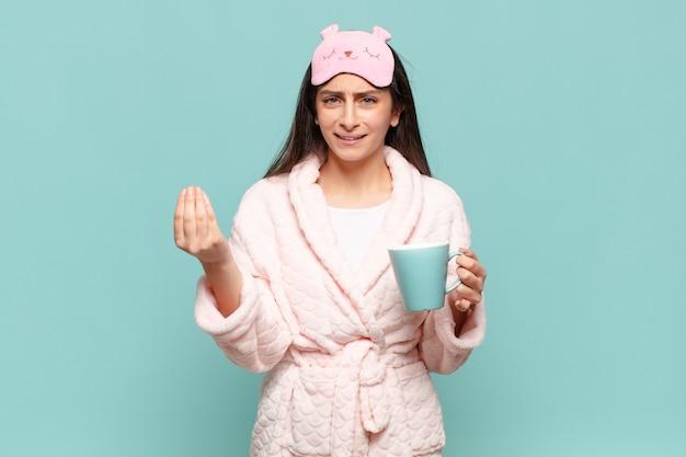 Mulher jovem bonita fazendo capice ou gesto de dinheiro, dizendo para você pagar suas dívidas! acordar de pijama conceito