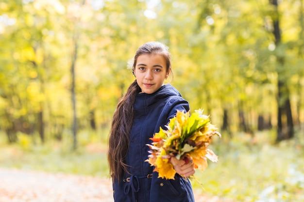Mulher jovem bonita feliz adolescente segurando buquê de folhas de outono e sorrindo, no fundo da floresta.