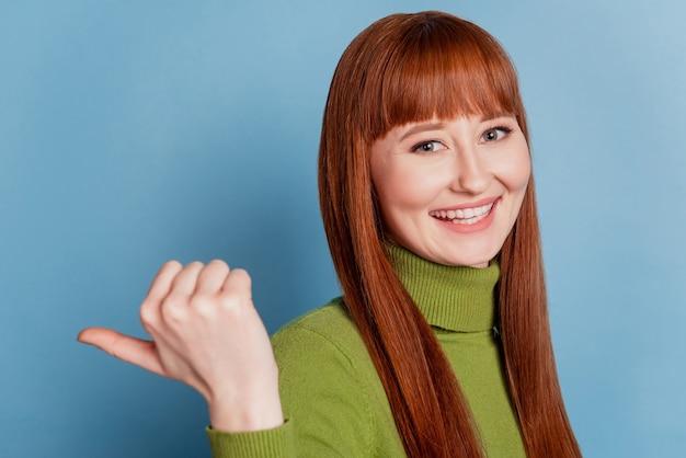 Mulher jovem bonita feliz apontar o fundo azul do espaço vazio com os dedos do polegar