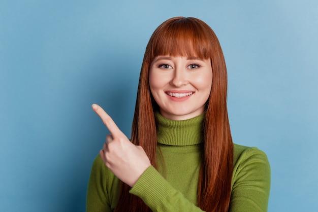 Mulher jovem bonita feliz apontar o fundo azul do espaço vazio com os dedos indicadores