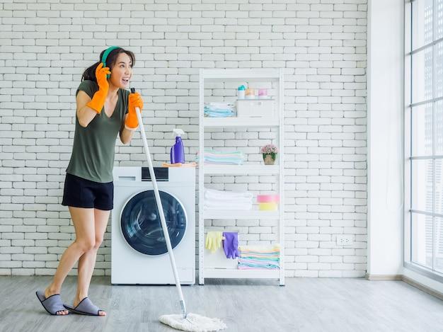 Mulher jovem bonita feliz, dona de casa usando luvas de borracha, chinelo e fone de ouvido verde cantando diversão com o esfregão como um microfone enquanto limpa o chão perto da máquina de lavar na parede branca.