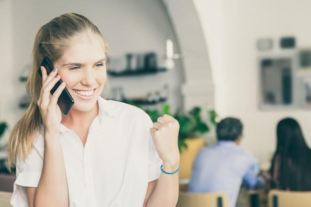 Mulher jovem bonita, feliz e bem-sucedida falando no celular, fazendo gesto de vencedor, em pé no espaço de trabalho conjunto