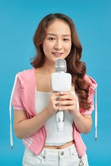 Mulher jovem, bonita, feliz e motivada, cantando uma música com um microfone,