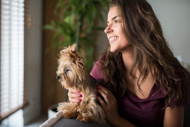 Mulher jovem bonita feliz olhando para a janela com o cachorro