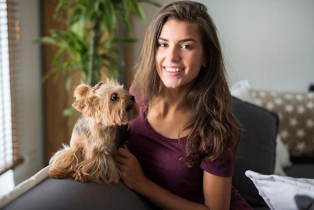 Mulher jovem bonita feliz posando com seu cachorrinho