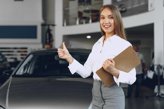 Mulher jovem bonita feliz revendedor de carros em showroom close-up