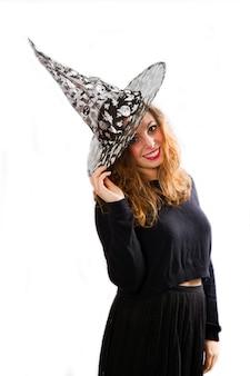 Mulher jovem bonita feliz sorrindo e chapéu de bruxa