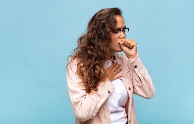 Mulher jovem bonita gesticulando na parede azul