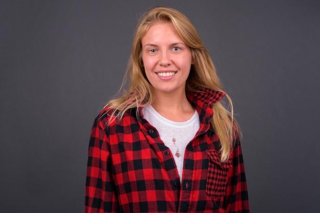 Mulher jovem bonita hippie com cabelo loiro contra uma parede cinza