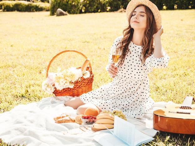 Mulher jovem bonita hippie com vestido de verão na moda e chapéu. mulher despreocupada fazendo piquenique do lado de fora.