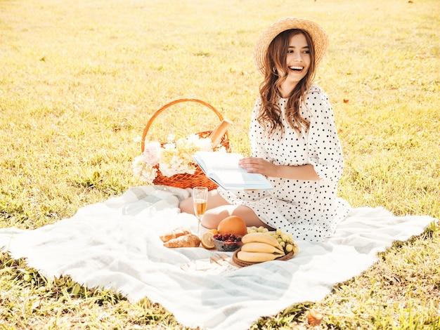 Mulher jovem bonita hippie em jeans da moda de verão, camiseta rosa e chapéu. mulher despreocupada fazendo piquenique do lado de fora.
