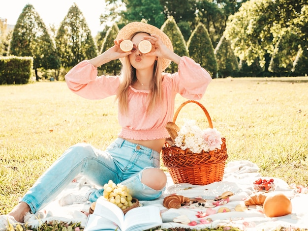 Mulher jovem bonita hippie em jeans da moda de verão, camiseta rosa e chapéu. mulher fazendo piquenique lá fora.