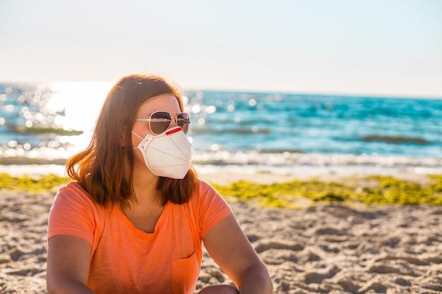 Mulher jovem bonita hippie em óculos de sol e máscara protetora. menina na moda em uma camiseta de verão.
