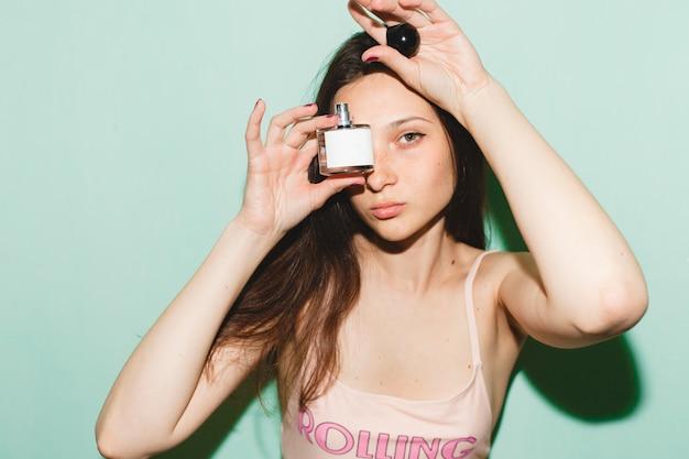Mulher jovem bonita hippie legal posando contra uma parede azul, segurando um frasco de perfume de perfume de água de banheiro