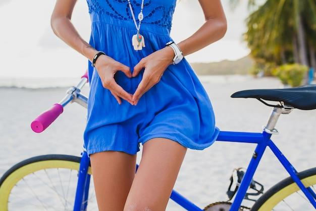 Mulher jovem bonita hippie posando com bicicleta na praia, mostrando o coração com as mãos