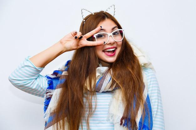 Mulher jovem bonita hippie posando contra uma parede branca, sorrindo se divertindo, cabelos longos brilhantes compõem, grande lenço aconchegante e orelhas de gato de festa engraçada. cores brilhantes, alegria, tempo positivo, inverno.