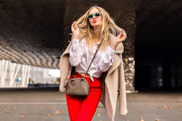 Mulher jovem bonita hippie posando na rua perto de centros de negócios modernos, vestindo roupa de escritório da moda e casaco de caxemira, enviando um beijo e aproveitou o dia fresco de outono, cores enfraquecidas.