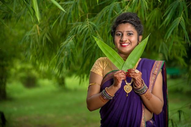 Mulher jovem bonita indiana tradicional em sari posando ao ar livre