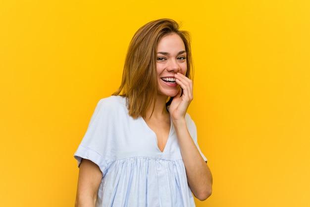 Mulher jovem bonita jovem rindo de algo, cobrindo a boca com as mãos.