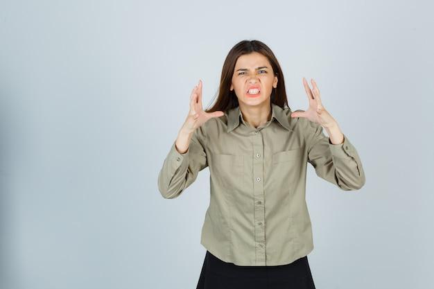 Mulher jovem bonita levantando as mãos de maneira agressiva, cerrando os dentes na camisa, saia e parecendo irritada. vista frontal.