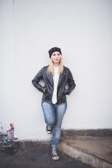 Mulher jovem bonita loira de cabelo liso na cidade encostada na parede
