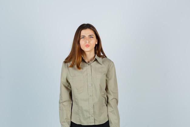 Mulher jovem bonita mantendo os lábios dobrados enquanto franzindo a testa na camisa e parecendo perplexo. vista frontal.
