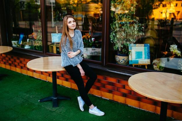 Mulher jovem bonita modelo com rosto sensual posando ao ar livre em frente a vitrine de loja com reflexões abstratas