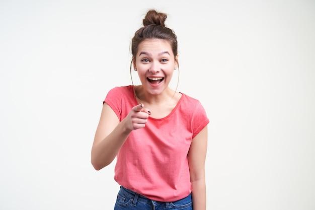 Mulher jovem bonita morena alegre com penteado casual rindo alegremente enquanto aponta para a câmera com o dedo indicador, isolado sobre um fundo branco em uma camiseta rosa