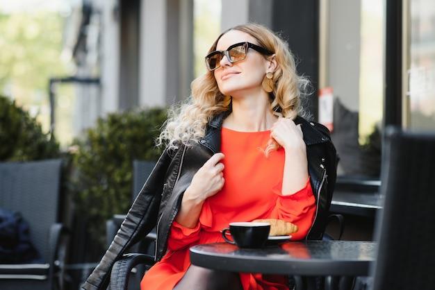 Mulher jovem, bonita, morena, com cabelos longos, usando um chapéu vermelho e vestido, bebendo um café em um café francês