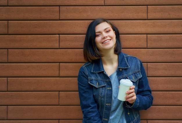 Mulher jovem bonita morena com túneis nas orelhas na jaqueta jeans em pé em frente a parede de tijolos, desfrutando de seu café quente.